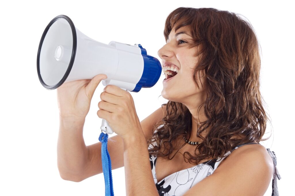 Girl speaking aloud using megaphones to reach her goal