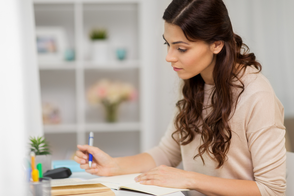 Women writing and deciding, making her list of top five new years resolutions.