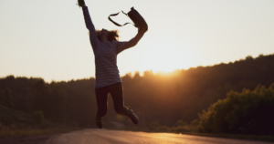 Less Stress Happy Jumping Woman Over Sunrise with Bag on Hand